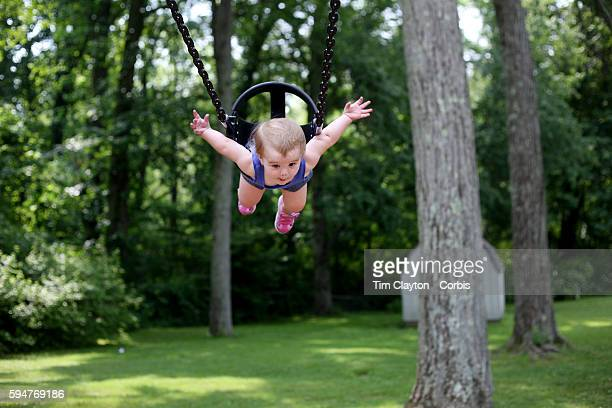 A fourteen month old baby girl enjoys playing on the swing in a playground setting during play Photo Tim Clayton