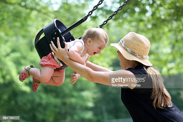 A fourteen month old baby girl enjoys playing on the swing with her mother in a playground setting during play Photo Tim Clayton