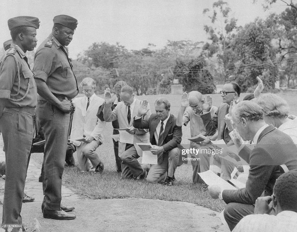 Fourteen whites, including five Britons and a woman kneel before President Idi Amin and vow to fight against South Africa as they are sworn into the Ugandan Army. The incident took place earlier this week.