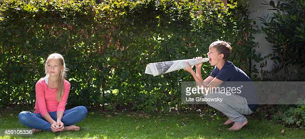 Fourteenyearold boy yelling through a megaphone made out of rolledup newspaper at his sister on August 11 in Duelmen Germany Photo by Ute...