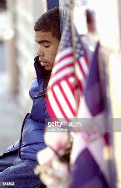Fourteenyearold Primitivo Espinal Jr sits next to a US flag and a Dominican flag at a makeshift memorial for the victims of American Airlines Flight...