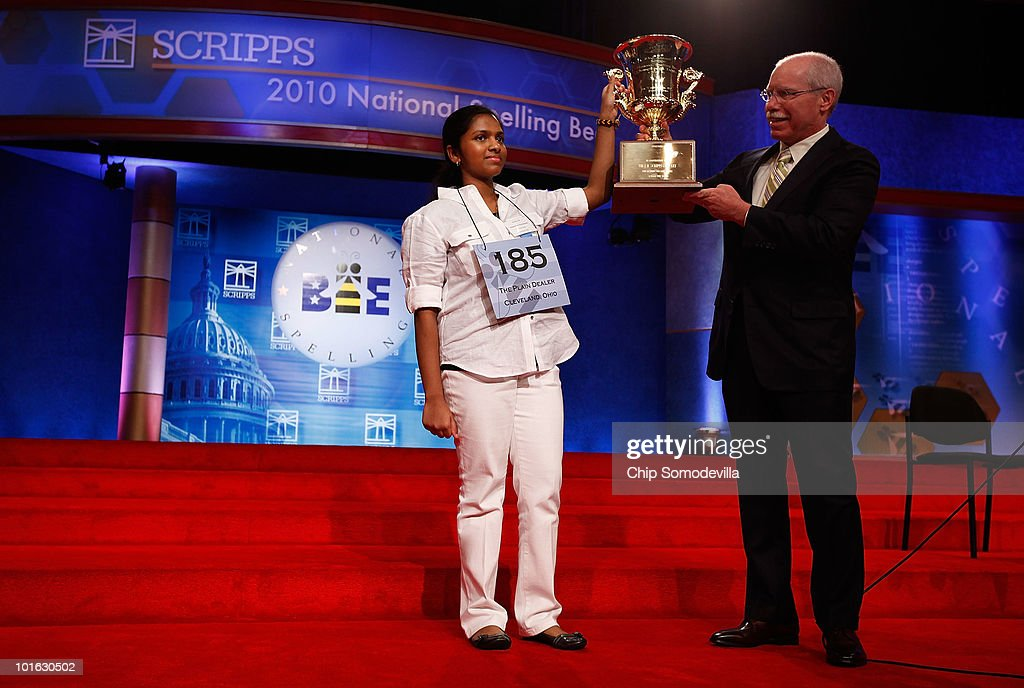 Fourteen-year-old Speller No. 185, Anamika Veeramani of Cleveland, Ohio, is handed her championship trophy by Scripps CEO Rich Boehne after winning the Scripps National Spelling Bee June 4, 2010 in Washington, DC. Veeramani spelled 'stromuhr' to win the competition.