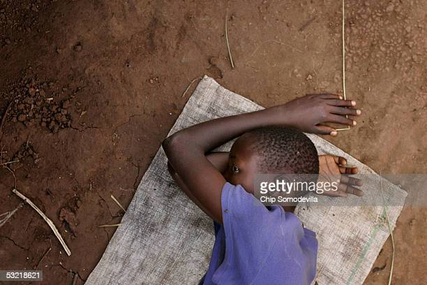 Fourteenyearold Susan lies on a food relief bag while suffering through a case of malaria June 5 2005 at the Railway Internally Displaced Persons...