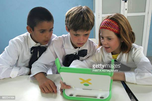Fourth degree schoolchildren discuss while working in the classroom with their laptops 07 December 2007 in Villa Cardal 80km from Montevideo The...