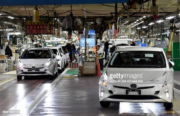 Fourth generation Toyota Prius cars are driven from the production line at the company's Tsutsumi assembly plant in Toyota City, Aichi prefecture on...