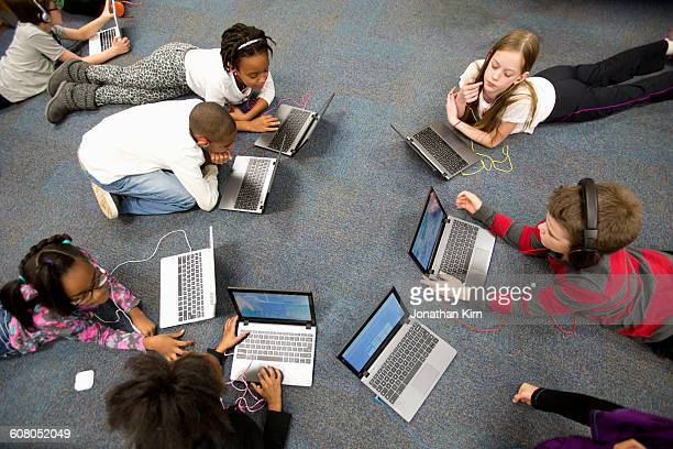 fourth grade students work on laptops in class. - education stock pictures, royalty-free photos & images