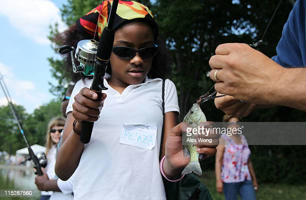 Fourth grader Me'aza Rivers of Ross Elementary School is helped to unhook the bluegill fish that she caught during a fishing event June 6 2011 at the...