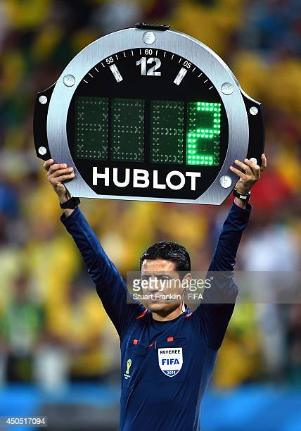 Fourth official Alireza Faghani displays the extra time during the 2014 FIFA World Cup Brazil Group A match between Brazil and Croatia at Arena de...