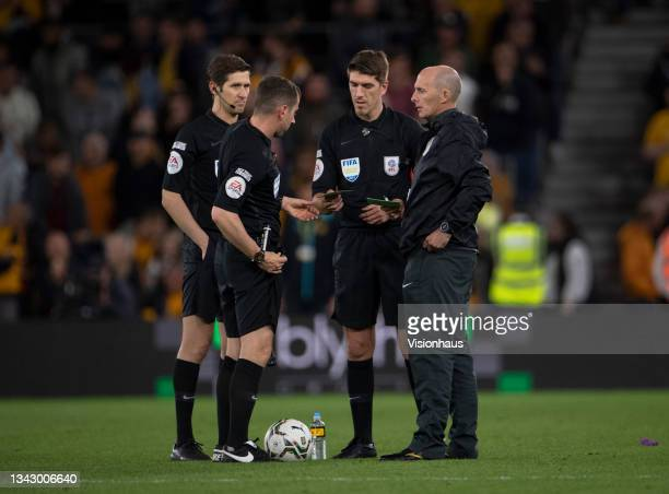 Fourth official Mike Dean talks to referee Peter Bankes and assistants Ian Hussin and Neil Davies after the Carabao Cup Third Round match between...