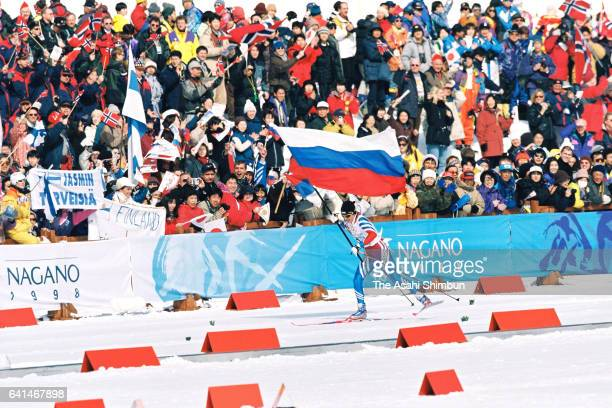 Fourth skiier Larisa Lazutina of Russia waving national flag to celebrate her team's win in the Cross Country Skiing Women's 4x5km Relay during day...