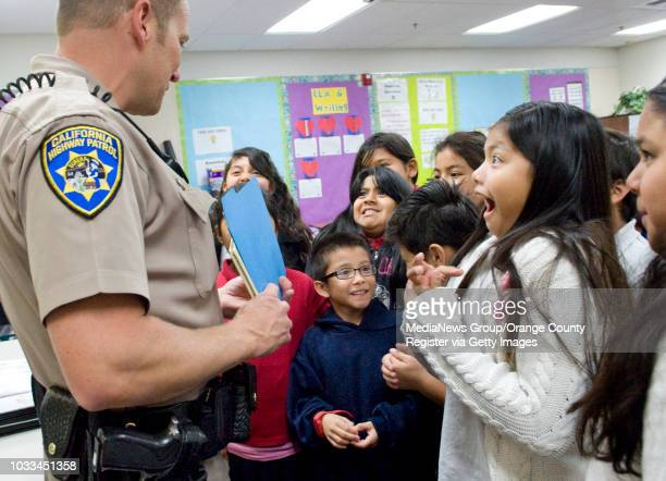 Fourthgrade students react to California Highway Patrolman Kevin Johnson after he reads Dr Seuss's Fox in Socks He was at Heroes Elementary School in...