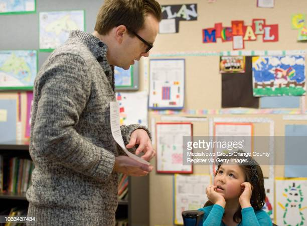 Fourthgrade teacher Chris McNatt explains an assignment tostudent Ruby Chriss at Stonegate Elementary School in Irvine shot 020314 rankingselem0216...