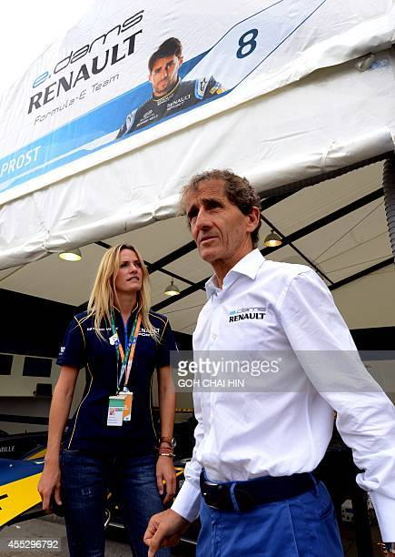 Fourtime French Formula One World Champion Alain Prost chats with an official at his edamsRenault team tent at the new Formula E venue near the...