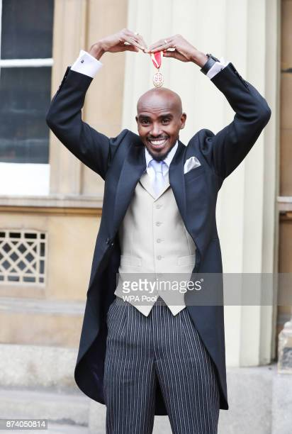 Fourtime Olympic champion Sir Mo Farah does the mobot after receiving his knighthood from Queen Elizabeth II at Buckingham Palace on November 14 2017...