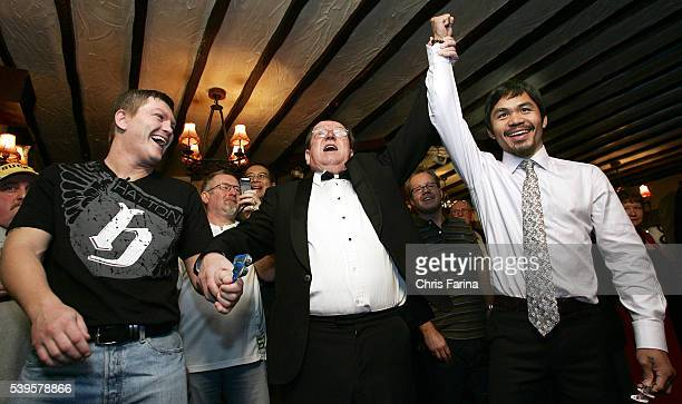 Fourtime world champion Manny 'Pacman' Pacquiao General SantosPhilippines gets his arm raised in victory as Ricky 'The Hitman' Hatton Manchester...
