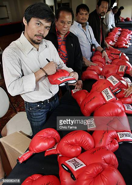 Fourtime world champion poundforpound king Manny Pacman Pacquiao signs hundreds of gloves before attending the exclusive red carpet Hollywood...