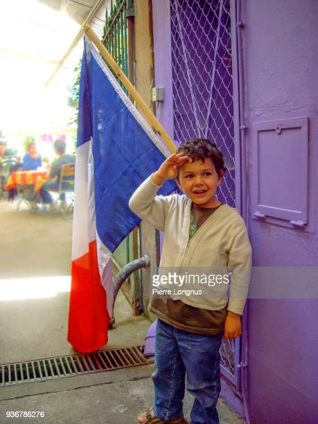 four-year-old boy doing a military salute standing by a french flag, during bastille day in france - haut rhin stock pictures, royalty-free photos & images