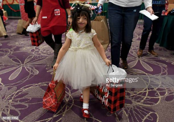 Fouryearold Divine Evers walks out with bags filled with gifts for her family during the MakeAWish Colorado 31st annual Holiday wish store at...