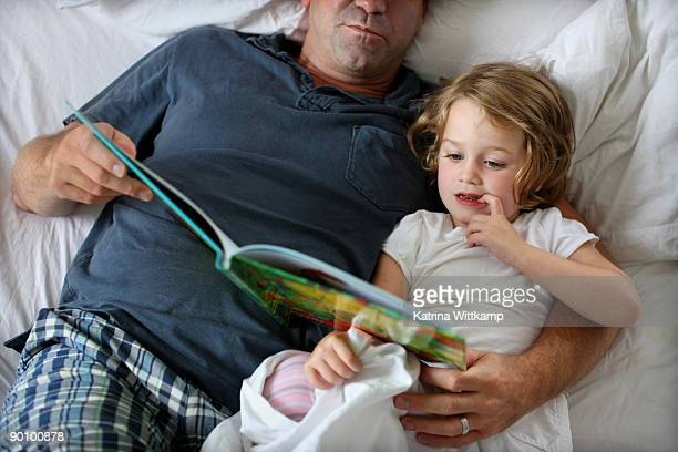 Four-year-old girl reading book with her dad.