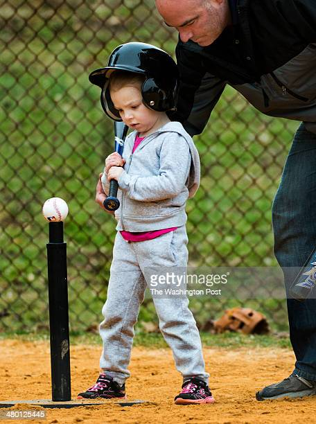 Fouryearold Kendall Hull sizes up the ball with coach Dan McKeon on the first day of coed Tball practice for boys and girls in Dunkirk MD on March 22...