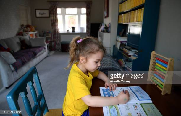Four-year-old Lois Copley-Jones, who is the photographer's daughter, does maths work with her mother on the first day of the nationwide school...