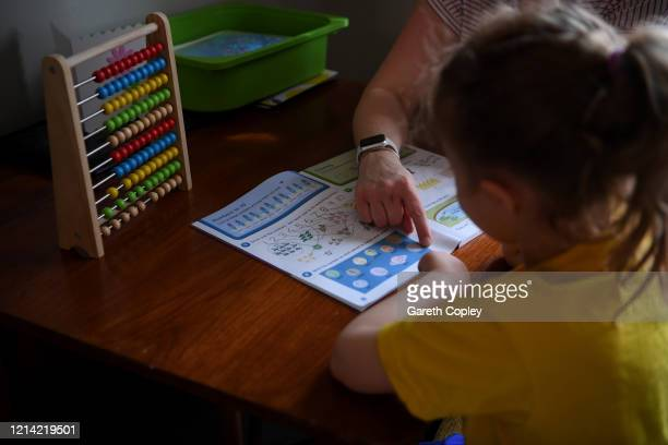 Fouryearold Lois CopleyJones who is the photographer's daughter does maths work with her mother on the first day of the nationwide school closures on...