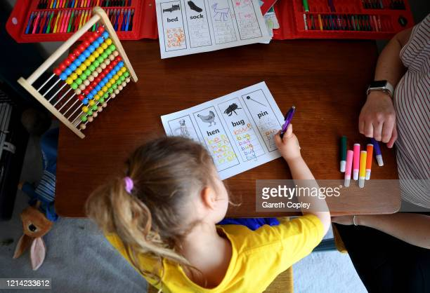 Four-year-old Lois Copley-Jones, who is the photographer's daughter, does phonics work with her mother on the first day of the nationwide school...