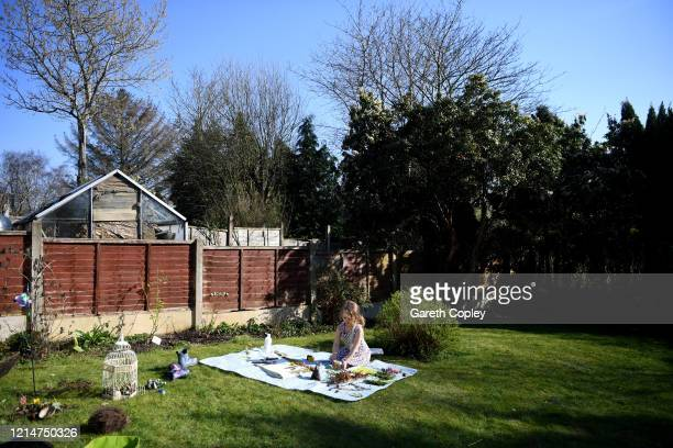 Fouryearold Lois CopleyJones who is the photographer's daughter does school work in garden on the third day of the nationwide school closures on...
