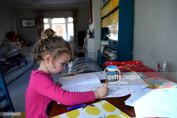 Fouryearold Lois CopleyJones who is the photographer's daughter does school work on the third day of the nationwide school closures on March 25 2020...