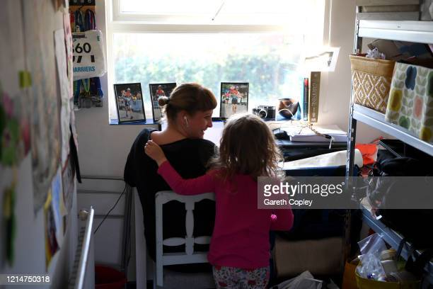 Four-year-old Lois Copley-Jones, who is the photographer's daughter, disturbs her mother Ruth, who is homeworking on the third day of the nationwide...