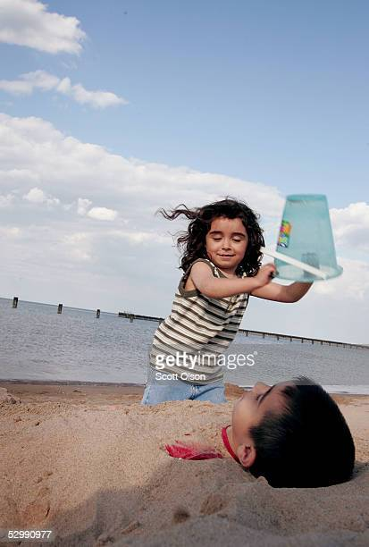 Four-year-old Rebecca Velazco buries her brother, six-year-old, Jorge Antonio in the sand at North Avenue Beach May 27, 2005 in Chicago, Illinois....