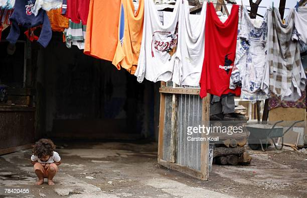 Fouryearold Roma refugee Zejnsa kneels in front of her family's home in the Cesmin Lug refugee camp in the Serbian district December 12 2007 in...