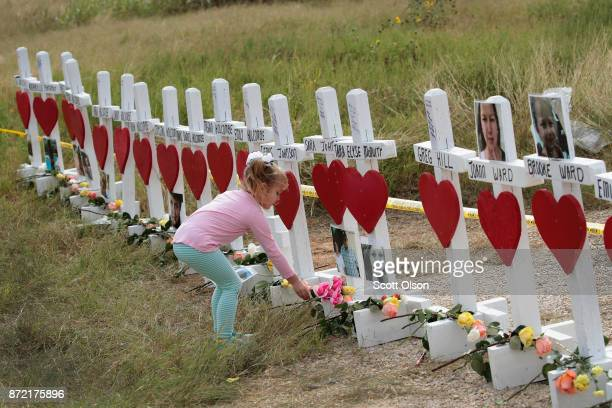 Fouryearold Shaelyn Gisler leaves a flower at a memorial where 26 crosses were placed to honor the 26 victims killed at the First Baptist Church of...