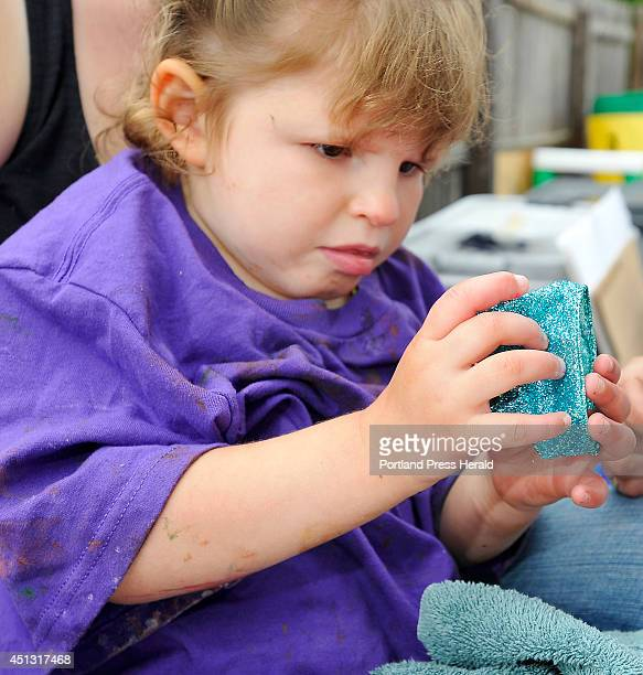 Fouryearold Tess Bigelow who has cortical visual impairment and developmental delays explores a wrist band made by art students from USM that is...