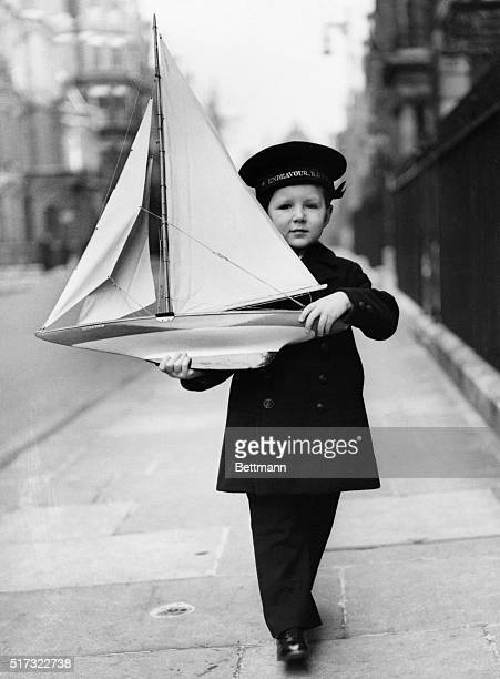 Fouryearold Tommy Sopwith wears proper naval attire to play with his model of the Endeavor a British yacht that vied for the America's Cup in 1934