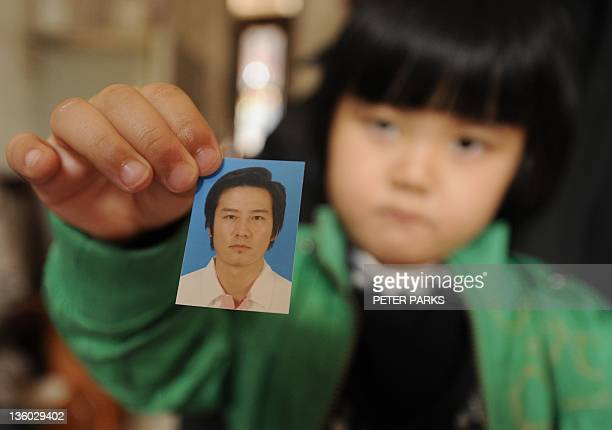 Fouryearold Zhang Jing Wen holds up a photograph of her father in her home in Wukan a fishing village in the southern province of Guangdong on...