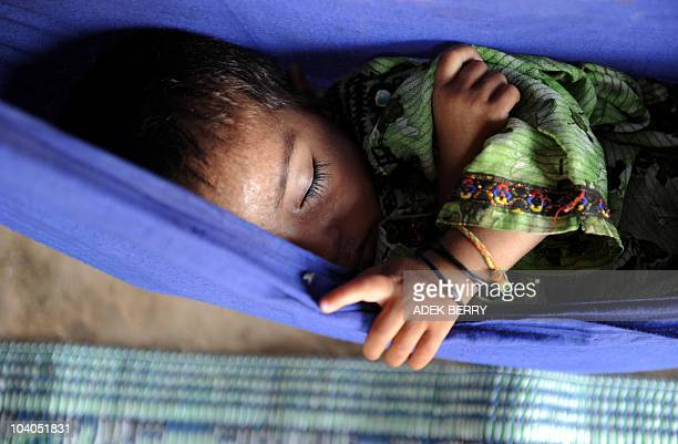 Four-year-old Zinath takes a nap in a makeshift hammock hanging in a tent at a camp in Sukkur on the second day of the Eid Al-Fitr celebration...