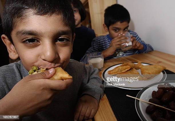 IMAGE 11/14/01 MISSISSAUGA ONTARIO Fouryearold Ziyaad Khan bites into a samosa one of the traditional foods Muslims break the daily fast with His...
