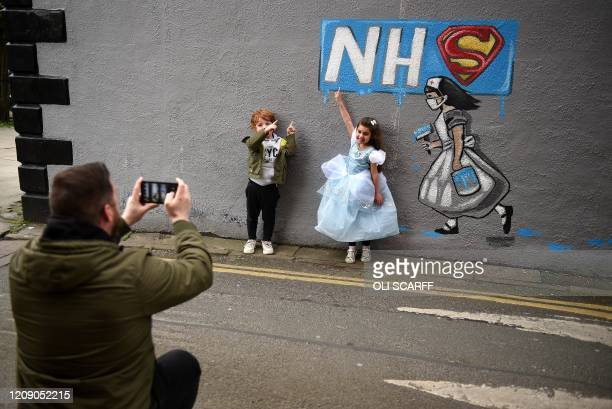 Fouryearolds George and Imaani pose for a photograoh with graffiti depicting the badge of the fictional super heros Superman and Superwoman and the...