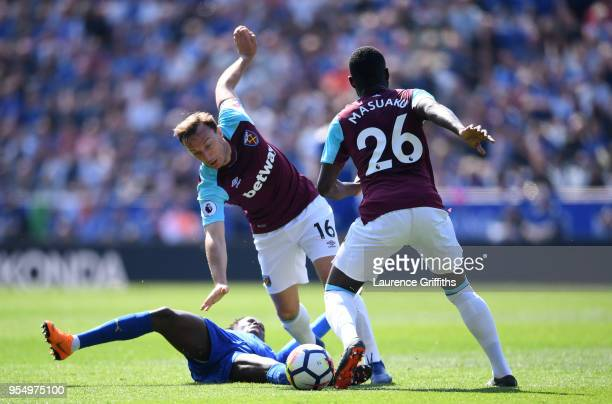 Fousseni Diabate of Leicester City goes down as Mark Noble and Arthur Masuaku of West Ham United control the ball during the Premier League match...