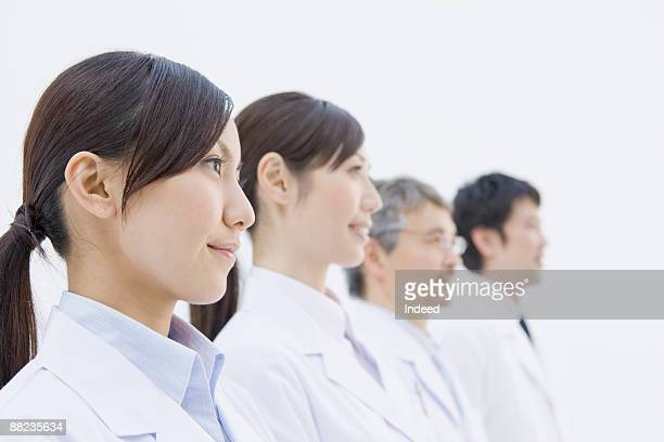 Fout scientists standing in a row, side view