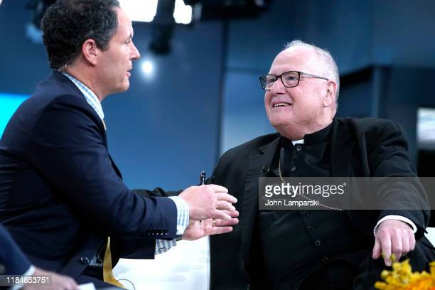 """Fox ancho Brian Kilmeade join Cardinal Timothy Dolan during """"Fox & Friends"""" at Fox News Channel Studios on October 31, 2019 in New York City."""