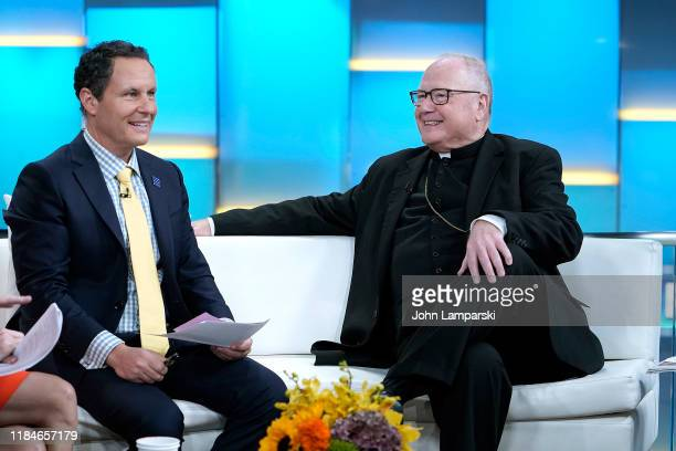 """Fox anchor Brian Kilmeade joins Cardinal Timothy Dolan during """"Fox & Friends"""" at Fox News Channel Studios on October 31, 2019 in New York City."""