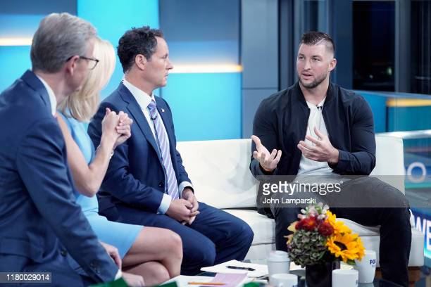 """Fox anchor Steve Doocy and Brian Kilmeade join Professional baseball player Tim Tebow during """"Fox & Friends"""" at Fox News Channel Studios on October..."""