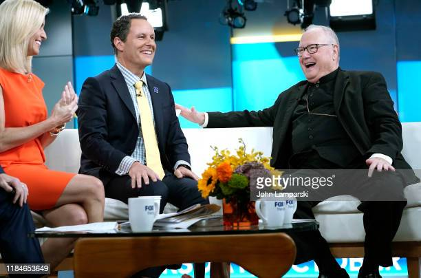 """Fox anchors Ainsley Earhardt and Brian Kilmeade join Cardinal Timothy Dolan during """"Fox & Friends"""" at Fox News Channel Studios on October 31, 2019 in..."""