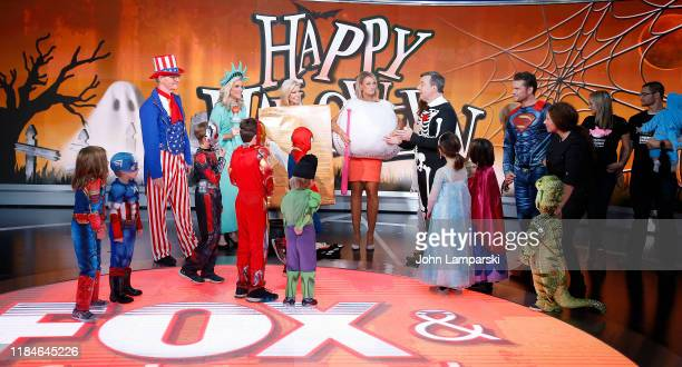 Fox anchors Steve Doocy Janice Dean Ainsley Earhardt Carley Shimkus Ed Henry Pete Hegseth and children participate in Fox Friends Halloween...
