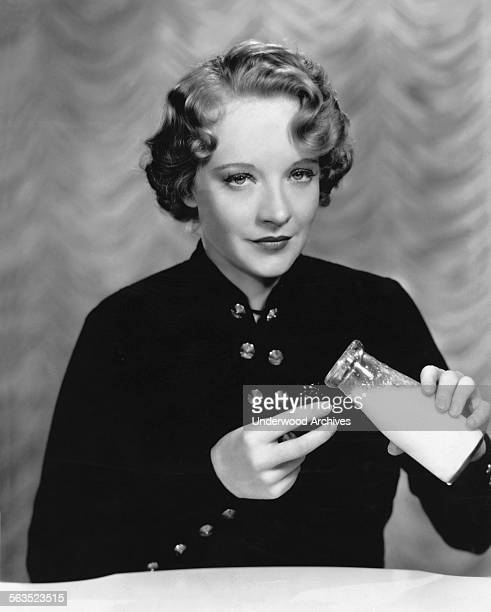 Fox Film actress Rosemary Ames uses a milk filled eye cup to soothe her eyes after a strenuous day on the set Hollywood California circa 1934