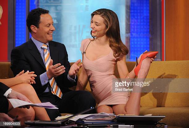 'Fox Friends' Television Host Brian Kilmeade looks on as Model Miranda Kerr demonstrates a yoga pose on 'Fox Friends' at FOX Studios on June 4 2013...
