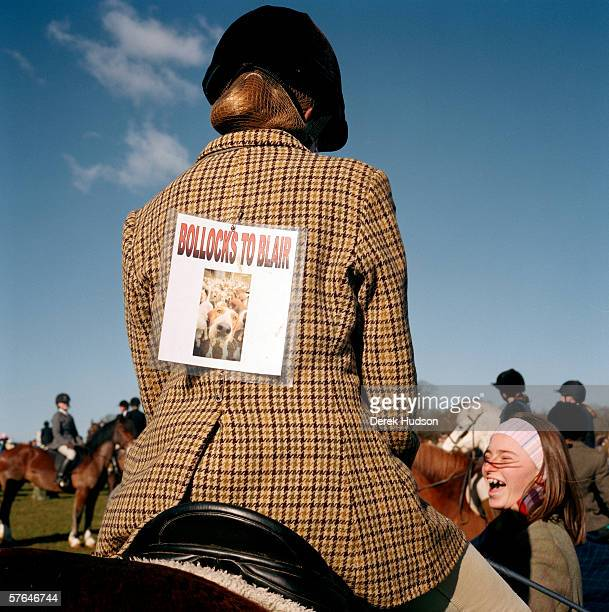 A fox hunter at a protest meeting the day after the ban on hunting with dogs in Britain came into effect with a notice pinned to her tweed riding...