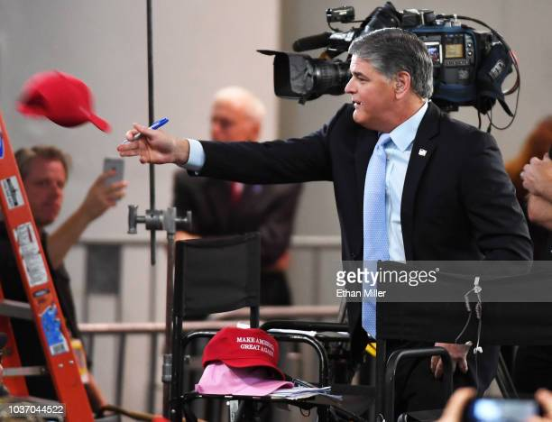 Fox News Channel and radio talk show host Sean Hannity throws a Trump hat that he autographed to an attendee before a Donald Trump campaign rally at...